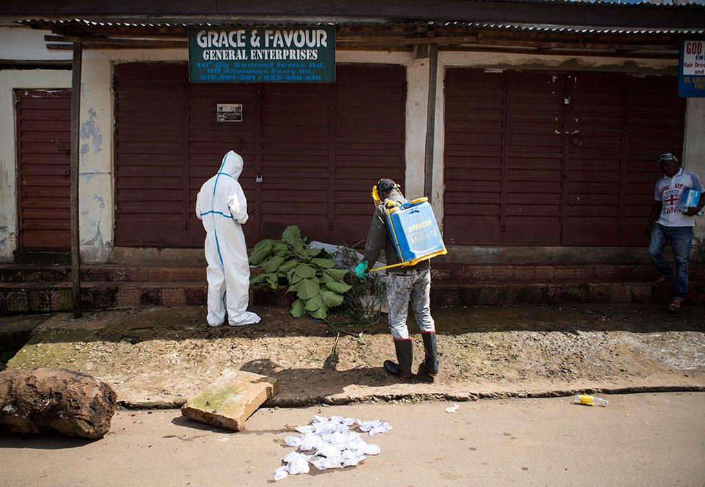 Медицинские работники из Сьерра-Леоне осматривают тело, предположительно, умершего от вируса Эбола.